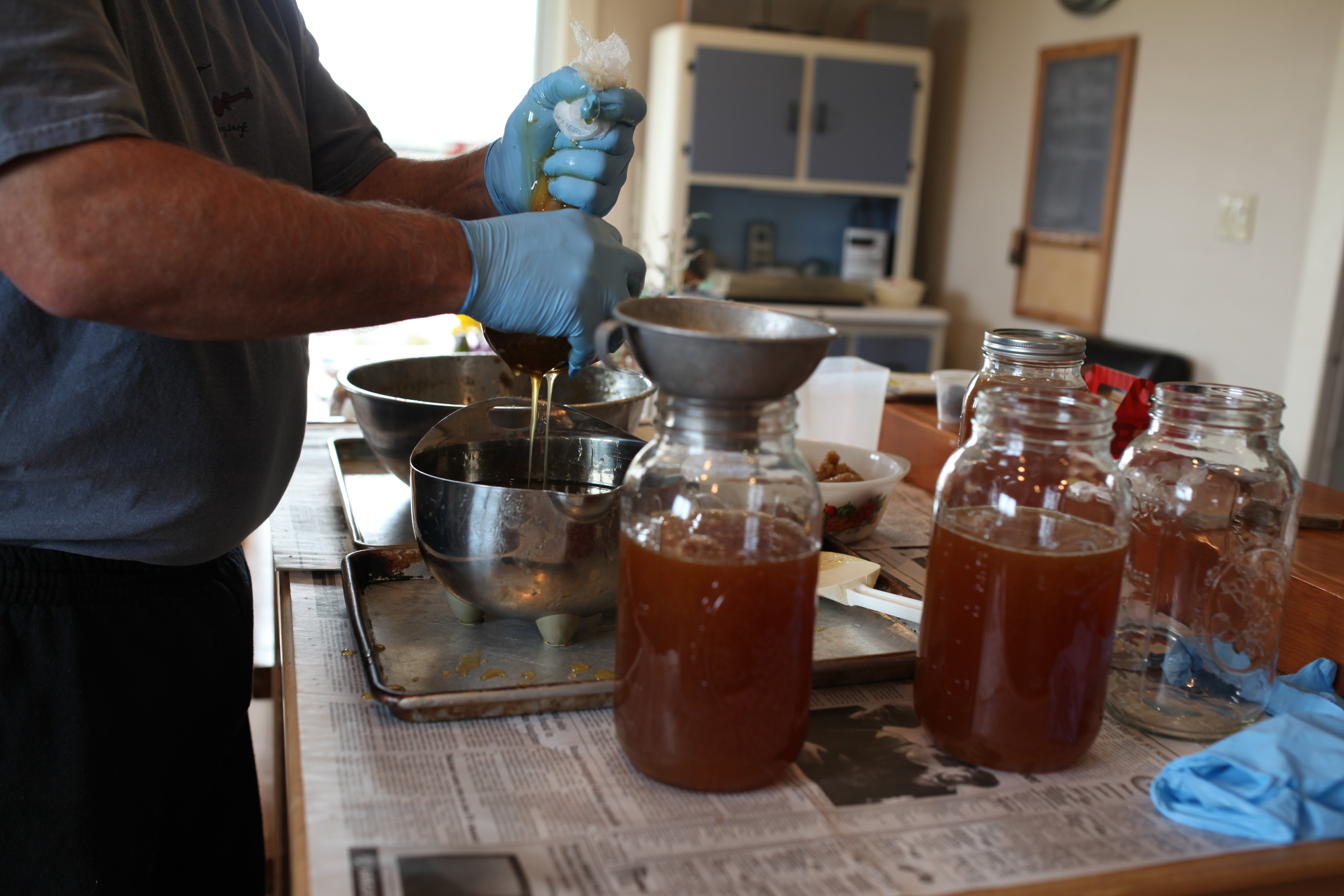 squeezing honey thru cheesecloth